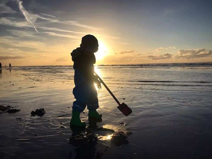 Silhouette Boy Digging Sand On Beach Against Sky During Sunset