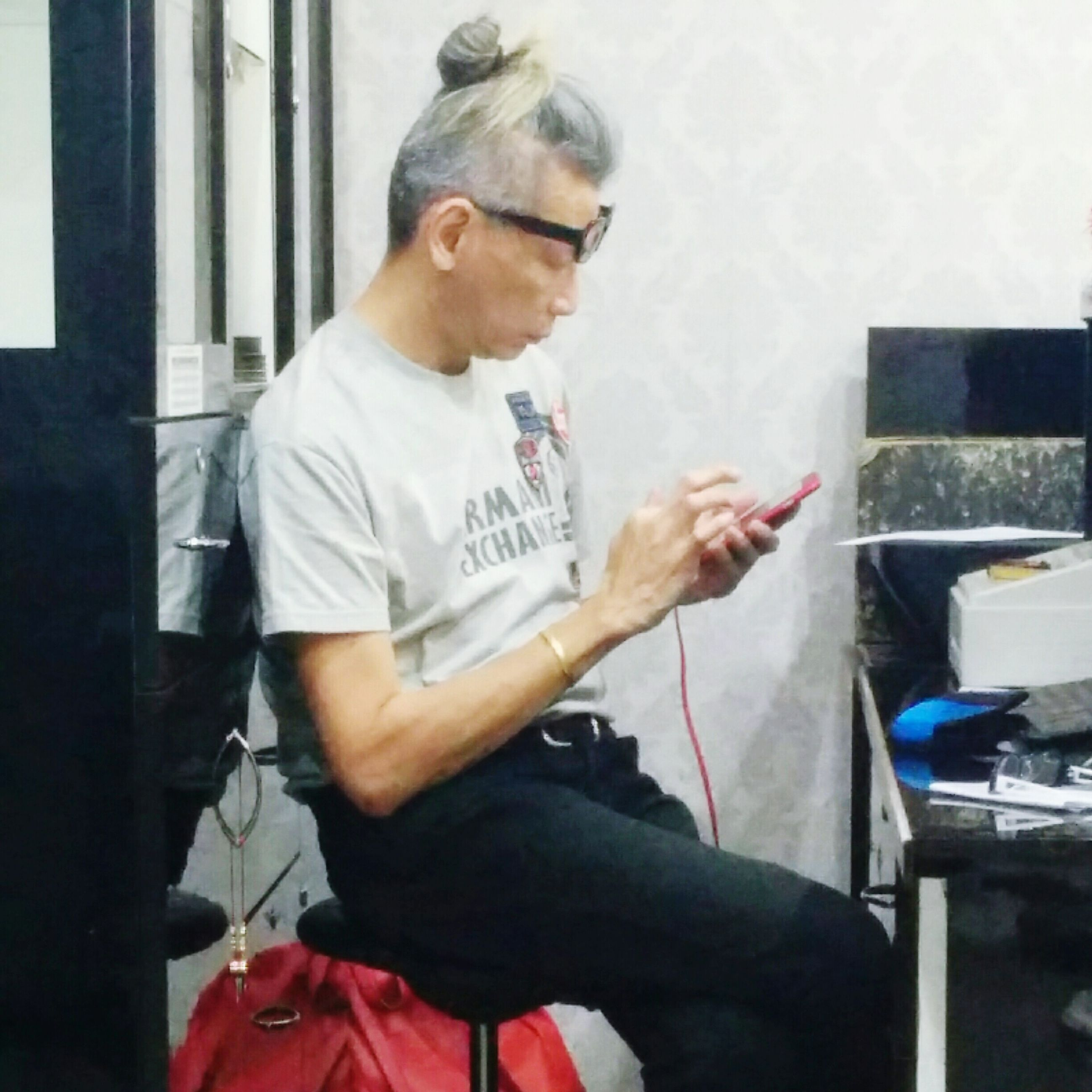 one person, three quarter length, sitting, casual clothing, real people, eyeglasses, music, indoors, day, technology, musician, one man only, people