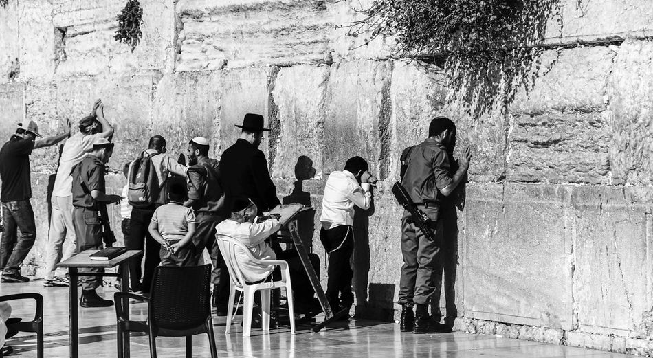 Rear view of people praying at wailing wall