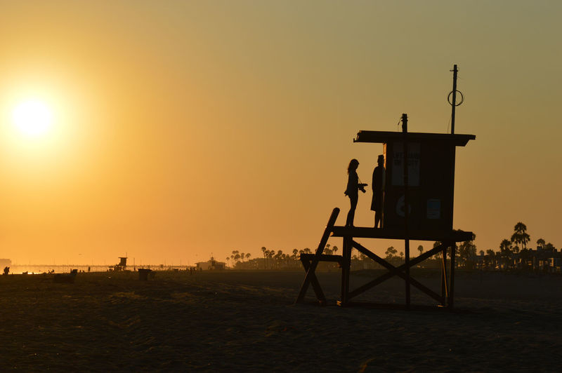 Silhouette Lifeguards On Hut At Beach Against Orange Sky