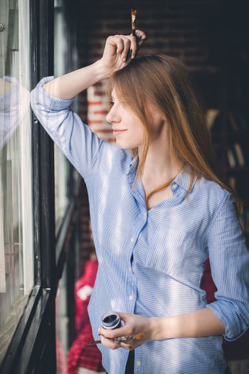 Young woman looking through window holding paintbrush