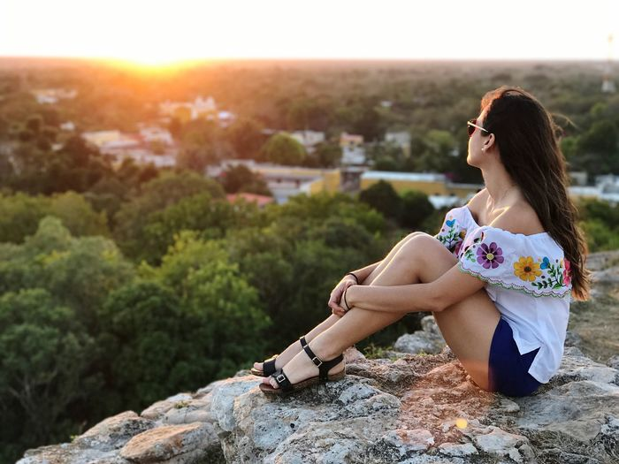 Young Woman Sitting On Mountain At Sunset