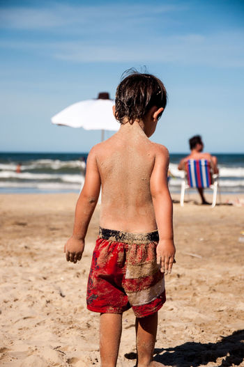 Rear view of shirtless boy walking at beach