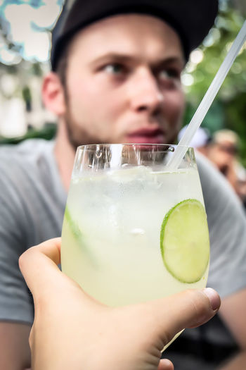 Cropped hand of woman holding drink by man at restaurant
