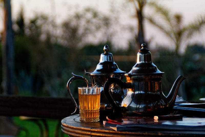Close-up of teapots by drink on table