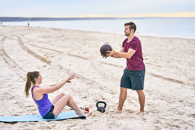 Friends Exercising With Medicine Ball On Sand At Beach