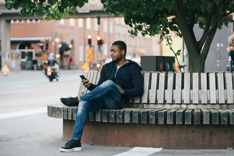 Man sitting on bench in city