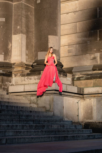 Full Length Of Woman Wearing Red Evening Gown Against Building
