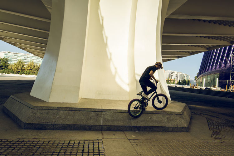 Man riding bicycle on bridge against buildings in city