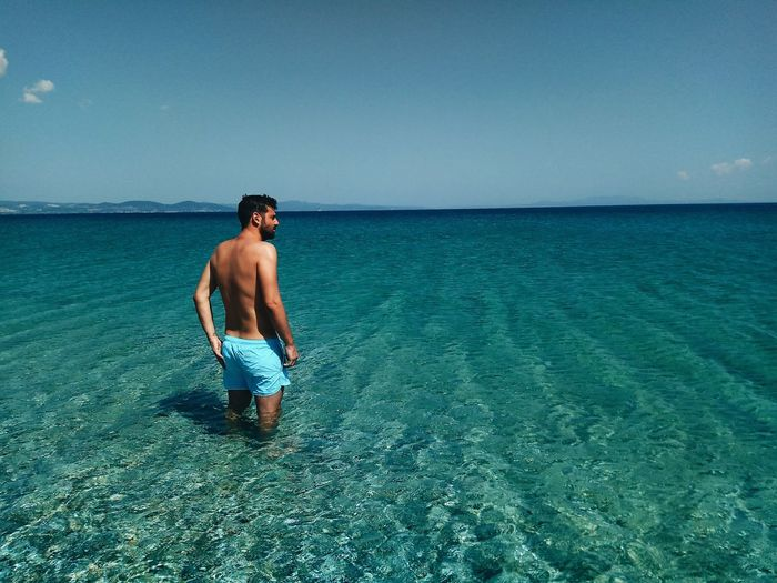 Rear view of shirtless man standing in sea against sky