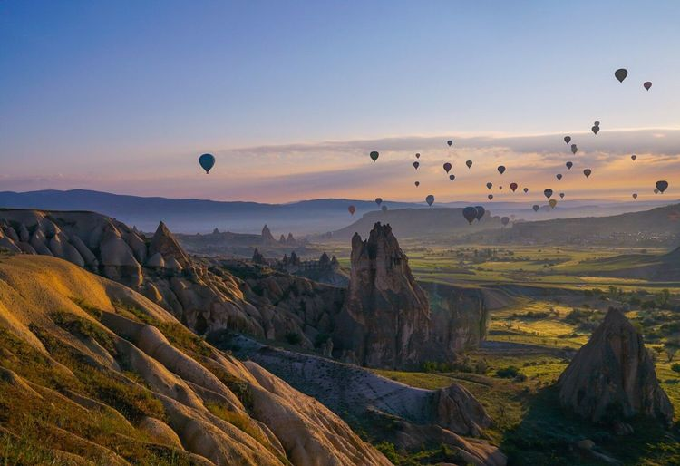 Hot Air Balloons Flying Over Mountain Landscape Against Sky