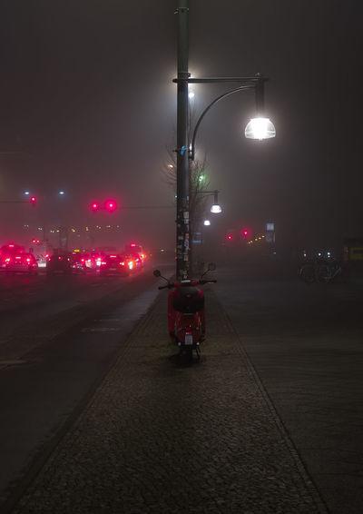 Illuminated street light on road in city at night