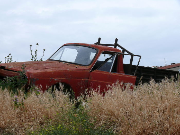 Abandoned Pick-Up Truck On Field Against Sky