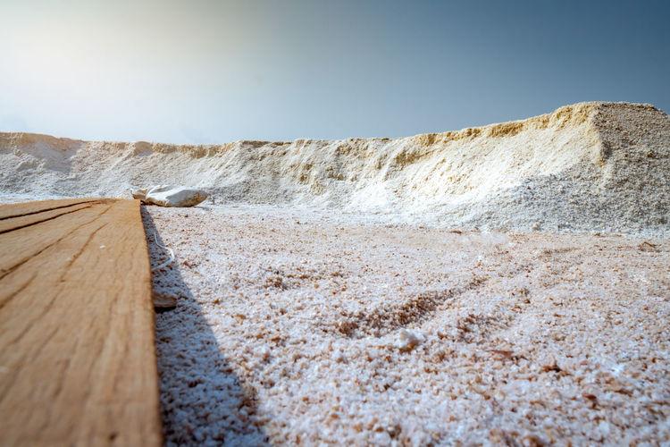 Low angle view of brine salt farm with blue sky. pile of organic sea salt near warehouse.