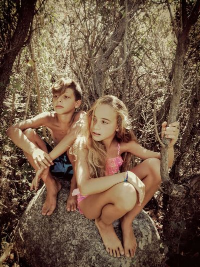 Siblings Sitting On Rock In Forest