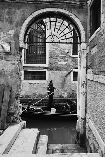 Rear view of man standing by old building