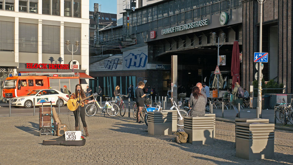 street musician at Friedrichstrasse Singer  Street Life Woman Building Exterior Built Structure City Day Female Guitar Musician Outdoors People Real People Songwriter Street Musicians Streetphotography Transportation Strassenfilm