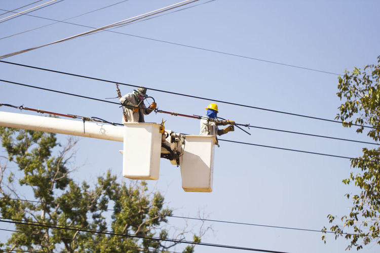 Low angle view of workers in cherry pickers repairing power line