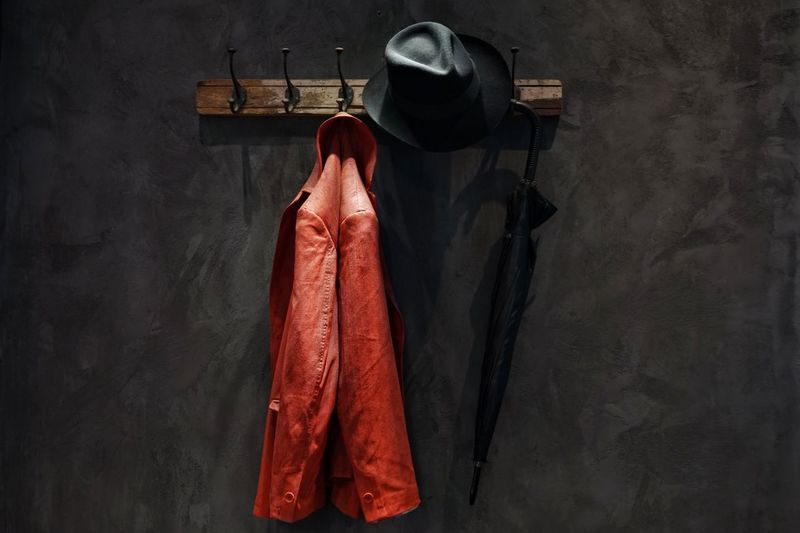 Close-up of jacket hanging on hook against wall