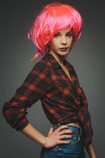 Portrait of beautiful young fashion model with wig against gray background