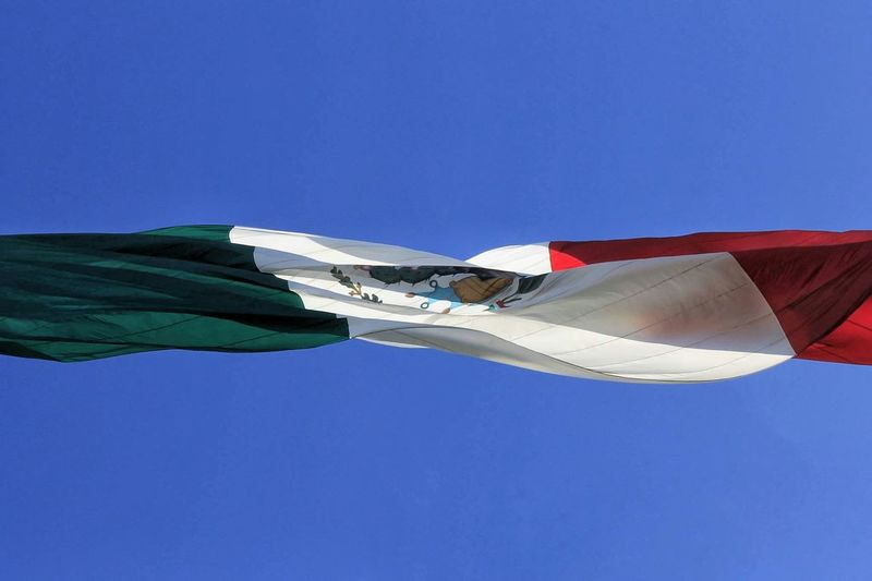 Low angle view of mexican flag against clear blue sky
