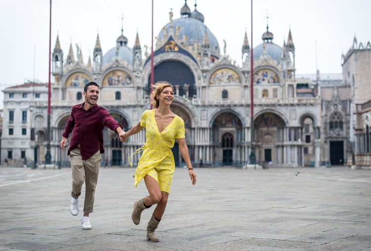 Smiling couple running against historic building