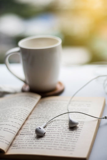 book ,Earphone And Coffee cup on white table. Earphon Morning Morning Light Music Reading Book Close-up Coffee Coffee - Drink Coffee Cup Communication Crockery Cup Drink Food And Drink Hot Drink Indoors  Mug Paper Publication Refreshment Selective Focus Table Tea Cup Text