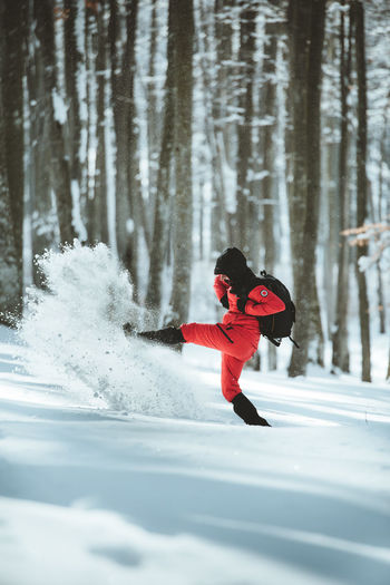 Cheerful male hiker playing in the snow. Man traveller having fun and hitting the snow Snow Cold Temperature Winter One Person Real People Full Length Tree Clothing Lifestyles Land Leisure Activity Day Plant Nature Motion Red Forest Warm Clothing Outdoors Fun Activity Hiking Cheerful Joy Foot