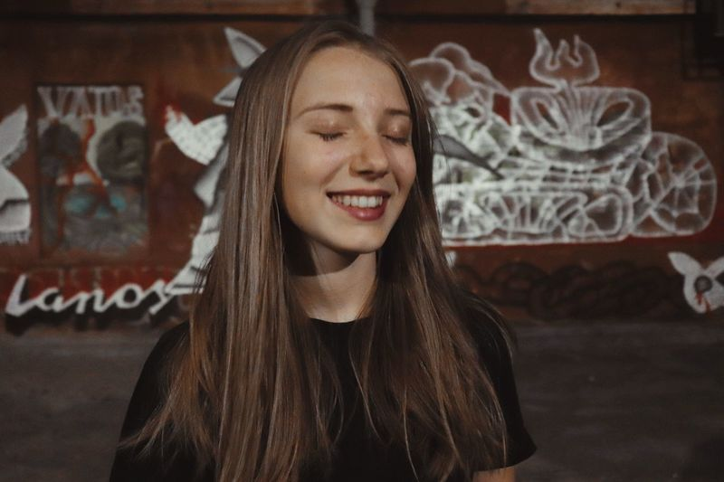 Smiling young woman with eyes closed against wall