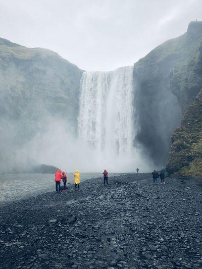People at waterfall against sky