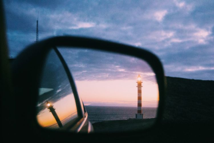 Reflection Of Light House Seen On Side-View Mirror Of Car During Sunset