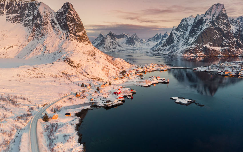 Aerial view of Scandinavian village on coastline in snowy valley at sunset Water Beauty In Nature Scenics - Nature Mountain Reflection Nature Lake Tranquil Scene Mountain Range Tranquility Cold Temperature Sky Winter Snow Non-urban Scene Sunset Idyllic Environment Snowcapped Mountain Formation