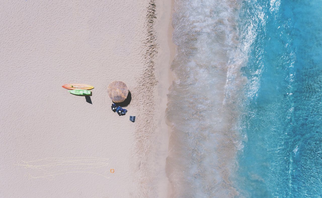 Aerial view of a beach with an umbrella and two surfboards