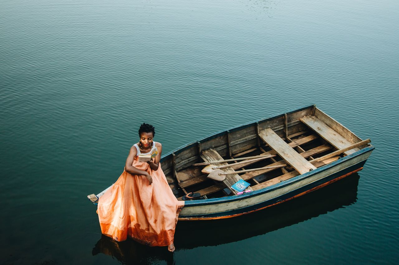High angle view of woman sitting on boat in sea