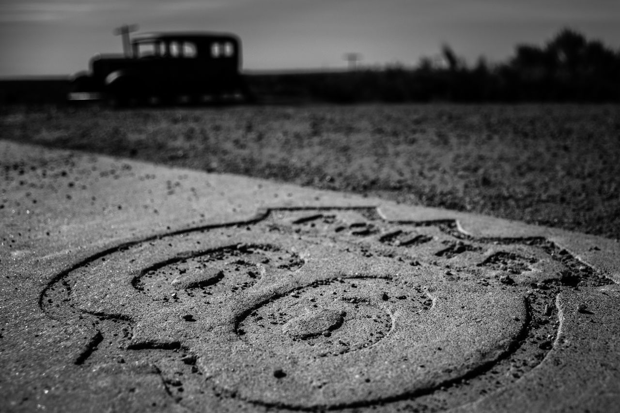 communication, focus on foreground, no people, transportation, selective focus, text, close-up, day, western script, road, land, car, mode of transportation, outdoors, nature, motor vehicle, creativity, sign, number, direction, message