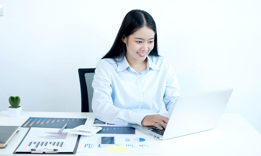 Smiling young woman using mobile phone on table