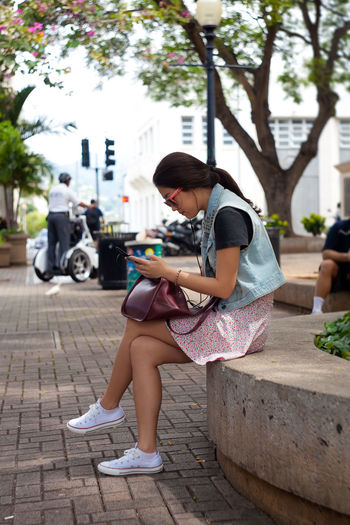 Side view of young woman using phone while sitting on retaining wall