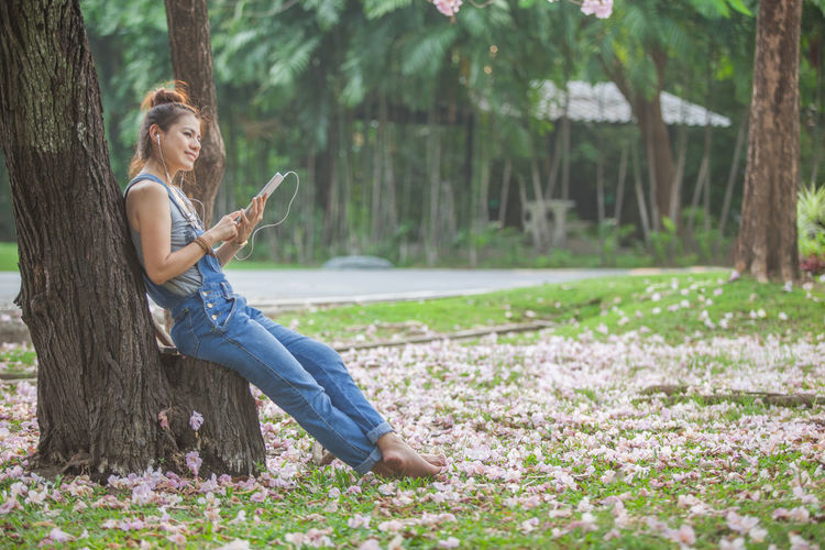 Side view of young man using phone while sitting on tree trunk