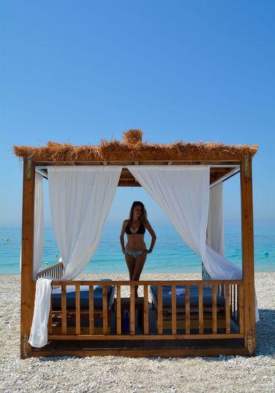 Woman wearing bikini standing at beach against clear blue sky