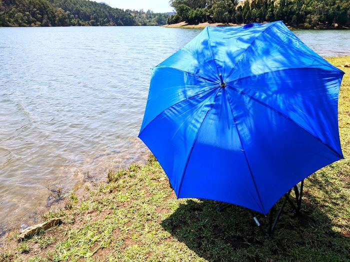 blue umbrella . Fishing EyeEm Selects Water Summer Protection Close-up Umbrella Sunshade Sun Lounger Lakeside Countryside Lounge Chair Shelter Calm Under