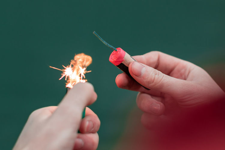 Cropped image of hands holding firecracker