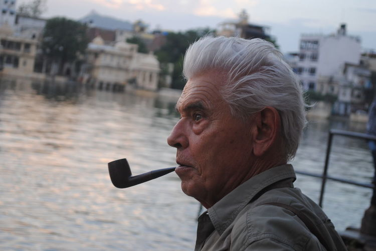 Close-Up Of Thoughtful Mature Man Smoking Pipe By River