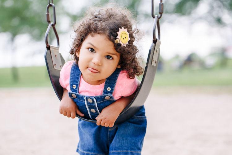 Full length portrait of cute girl swinging at park