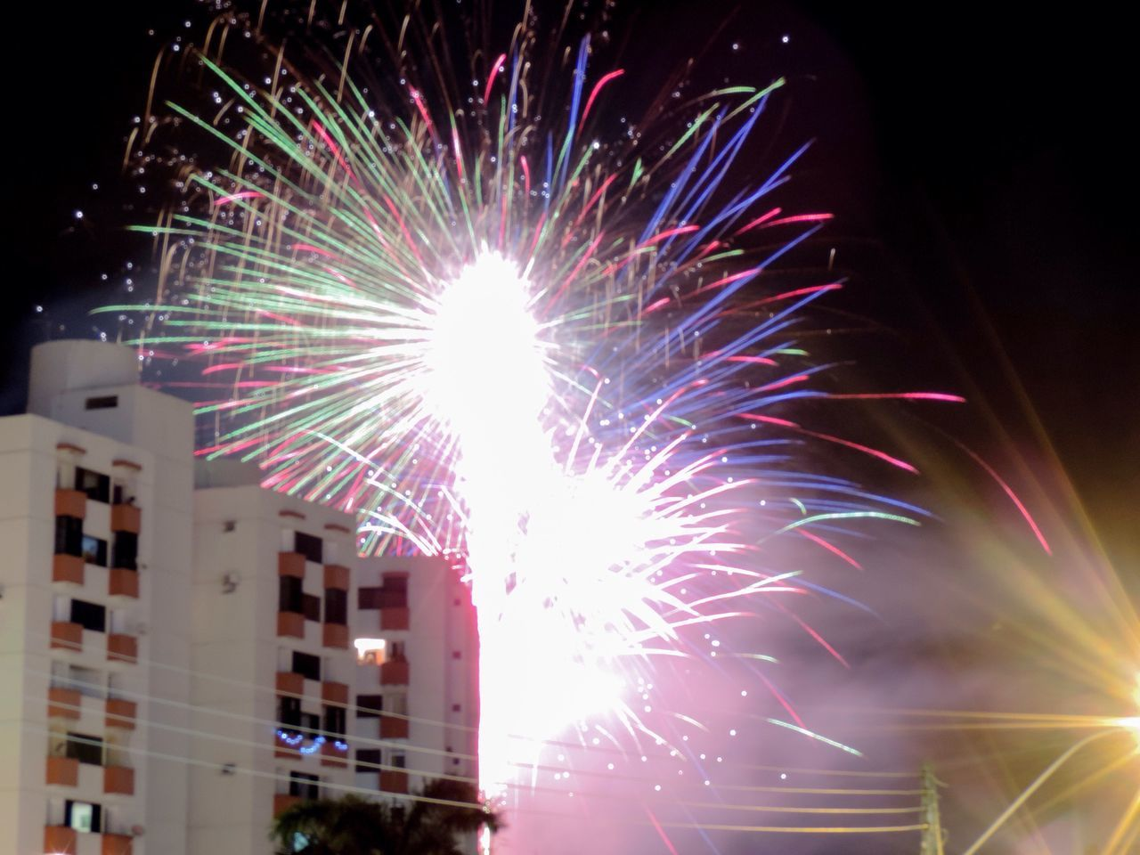 celebration, night, firework display, firework - man made object, event, illuminated, exploding, arts culture and entertainment, glowing, low angle view, long exposure, firework, architecture, building exterior, motion, blurred motion, outdoors, built structure, celebration event, multi colored, no people, sky, city