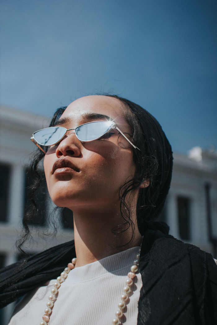Close-up of young woman wearing sunglasses against blue sky