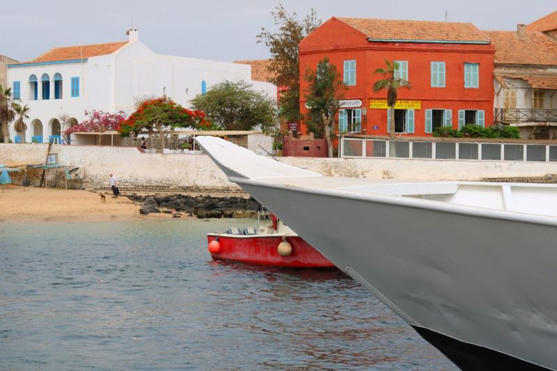 Boat moored on sea by houses against buildings