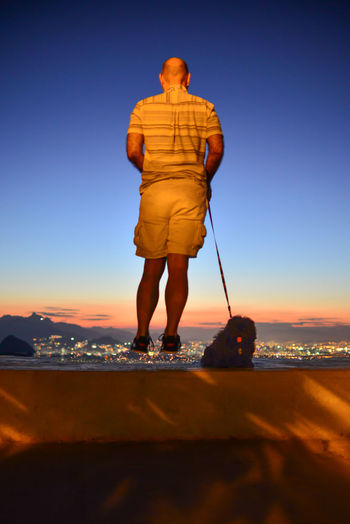 Rear View Of Man Jumping By Dog On Retaining Wall During Sunset