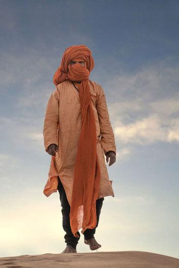 Full length of woman standing against sky