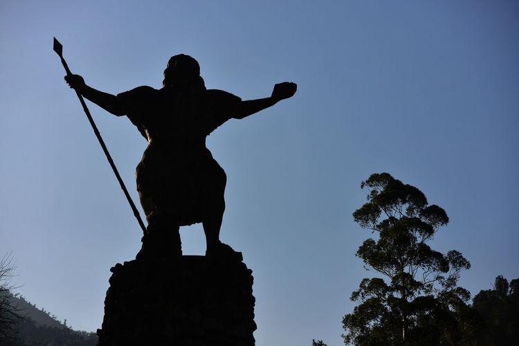 """Monumento al Indio. El Chasqui, más popularmente conocido como Monumento al Indio o el Indio, es una escultura de 6 metros de altura emplazada sobre una base de 10 metros y a su vez ubicada a la altitud de 1.100 metros dentro de la reserva provincial Los Sosa en la ruta provincial 307 hacia Tafí del Valle y Amaicha del Valle en Tucumán. En el basamento de la obra hay una alegoría del """"Himno al Sol"""". En el amanecer un sacerdote indígena se inclina ante el astro y un poeta le ofrece música y canto. También están el amor maternal, simbolizado por una madre y su hijo; el sentir religioso, que encarna una pareja de promesantes, y un guerrero que deja su lanza y se pliega a la ceremonia. Por fin, """"el mandinga"""" que cae al abismo, representa la luz del sol disipando las tinieblas. La obra fue realizada por Enrique Prat Gay y fue instalada en enero de 1943. Dicho escultor es el autor del busto de Zenón Santillán ubicado en el edificio de la municipalidad de San Miguel de Tucumán; el de Yrigoyen que está en la escuela del mismo nombre; y el de Nicolás Avellaneda, en el parque Avellaneda. Amigo de Lola Mora, se formó en Italia como ella. La obra fue restaurada en julio de 2008. La palabra chasqui viene del idioma quechua, y significa """"mensajero, agente de correo, transportador"""". Argentina Art Blue Clear Sky Creativity Day Low Angle View Monument Nature No People Outdoors Sculpture Sky Statue Tafí Del Valle Tranquility Tree Tucumán"""