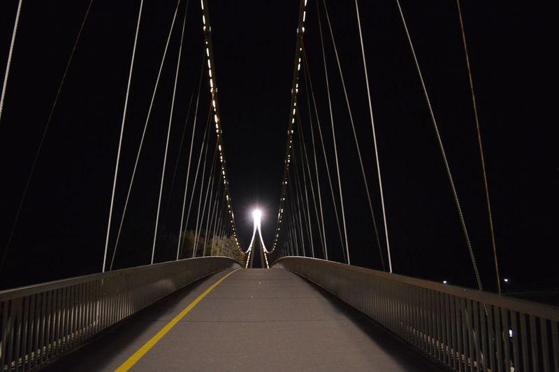 Illuminated footbridge against clear sky at night